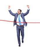 Homme d'affaires heureux courant par la ligne d'arrivée Image stock