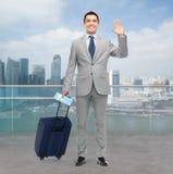 Homme d'affaires heureux dans le costume avec le sac de voyage Images stock