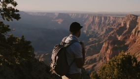 Homme d'affaires heureux de mouvement lent jeune avec le sac à dos augmentant des vacances au panorama épique de coucher du solei clips vidéos
