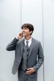 Homme d'affaires heureux de sourire dans le costume ayant une conversation de téléphone portable Images libres de droits