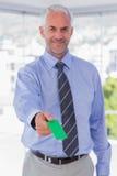 Homme d'affaires heureux donnant la carte de visite professionnelle de visite verte photo libre de droits