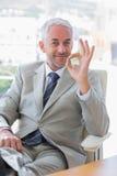 Homme d'affaires heureux donnant le signe correct Images stock