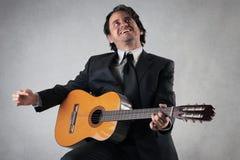 Homme d'affaires heureux jouant la guitare Photos stock