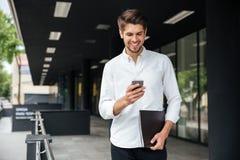 Homme d'affaires heureux marchant et à l'aide du téléphone portable dehors photos stock