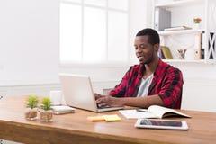 Homme d'affaires heureux noir de sourire dans le bureau occasionnel, travail avec l'ordinateur portable Photos libres de droits