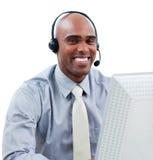 Homme d'affaires heureux parlant sur l'écouteur à un ordinateur images libres de droits