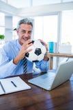 Homme d'affaires heureux regardant l'appareil-photo et tenant la boule de pied Photographie stock