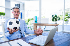 Homme d'affaires heureux regardant l'appareil-photo et tenant la boule de pied Photo stock