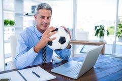 Homme d'affaires heureux regardant l'appareil-photo et tenant la boule de pied Photos libres de droits