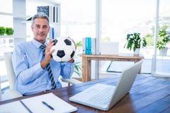 Homme d'affaires heureux regardant l'appareil-photo et tenant la boule de pied Image libre de droits