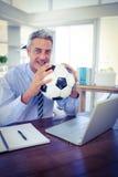 Homme d'affaires heureux regardant l'appareil-photo et tenant la boule de pied Photos stock