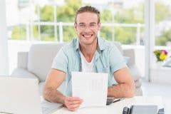 Homme d'affaires heureux s'asseyant à son bureau tenant le document Photo libre de droits