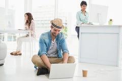 Homme d'affaires heureux s'asseyant sur le plancher utilisant l'ordinateur portable Image stock