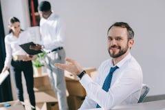 homme d'affaires heureux souriant aux collègues de moment de caméra se tenant derrière photo libre de droits