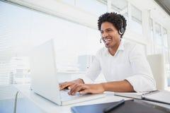 Homme d'affaires heureux travaillant à son casque de port de bureau Photo libre de droits