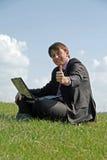 Homme d'affaires heureux travaillant avec un ordinateur portatif extérieur Images stock