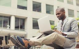 Homme d'affaires heureux travaillant sur l'ordinateur portable dehors Photographie stock