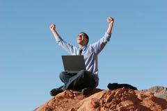 Homme d'affaires heureux travaillant sur l'ordinateur portatif Image stock