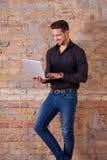 Homme d'affaires heureux utilisant l'ordinateur portable photographie stock