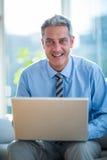 Homme d'affaires heureux utilisant l'ordinateur portable Photo stock