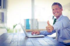 Homme d'affaires heureux utilisant l'ordinateur portable et regarder l'appareil-photo avec des pouces  Photographie stock libre de droits