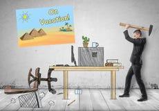 Homme d'affaires heurtant son lieu de travail avec le marteau Images libres de droits
