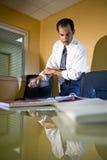 Homme d'affaires hispanique dans le roulement de bureau vers le haut des chemises photographie stock