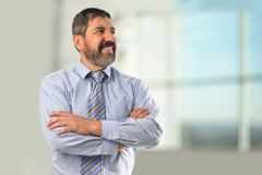 Homme d'affaires hispanique Smiling avec des bras croisés Photographie stock libre de droits