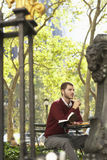 Homme d'affaires Holding Book And Pen In Park Photo libre de droits