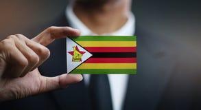 Homme d'affaires Holding Card de drapeau du Zimbabwe images libres de droits