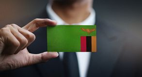 Homme d'affaires Holding Card de drapeau de la Zambie photographie stock
