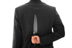 Homme d'affaires Holding Knife Behind son image conceptuelle arrière d'isolement Image libre de droits