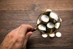 Homme d'affaires Holding Magnifying Glass au-dessus des pièces de monnaie Photographie stock libre de droits