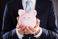 Homme d'affaires Holding Piggybank Photos libres de droits