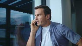 Homme d'affaires hurlant sur le mobile dans la maison Homme choqué par plan rapproché parlant au téléphone banque de vidéos