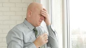 Homme d'affaires Image Suffering un mal de tête avec un verre avec de l'eau à disposition photographie stock