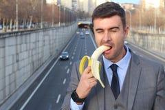 Homme d'affaires inadéquat drôle mordant une banane photographie stock