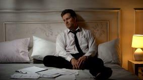 Homme d'affaires indifférent s'asseyant autour des documents sur le lit, désir de changer le travail image stock