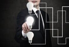 Homme d'affaires indiquant la lampe à lueur Image libre de droits