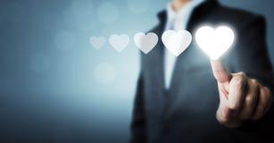 Homme d'affaires indiquant le symbole blanc de coeur l'estimation d'augmentation du Fe Photographie stock libre de droits