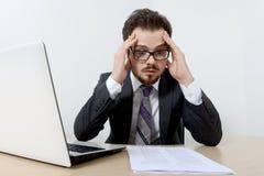 Homme d'affaires inquiété avec l'ordinateur portable et le document Image libre de droits