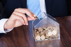 Homme d'affaires insérant la pièce de monnaie dans la boîte Images stock