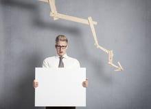 Homme d'affaires intéressé présent le panneau devant descendre g photographie stock libre de droits