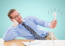 Homme d'affaires irrité tenant le récepteur téléphonique au bureau photographie stock