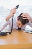 Homme d'affaires irrité tenant le téléphone photo libre de droits