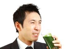 Homme d'affaires japonais avec le jus de légumes vert Image libre de droits