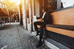 Homme d'affaires japonais avec le netbook dehors en café de rue Photo stock