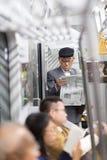 Homme d'affaires japonais faisant le tour au travail dans le matin, le transport en commun intérieur debout et lisant le journal Photo stock