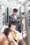 Homme d'affaires japonais faisant le tour au travail dans le matin, le transport en commun intérieur debout et lisant le journal Image libre de droits