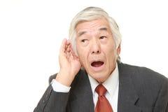 Homme d'affaires japonais supérieur avec la main derrière l'oreille écoutant étroitement Photo libre de droits